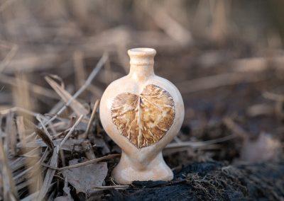 Urn hartvorm met een bruin boomblad, zijde 2